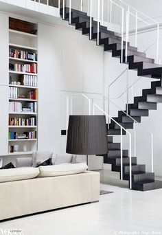 A bookcase neatly slots into a wall beneath the graphic laminated steel staircase by Fratelli Ronchetti in this early 1900s theatre-turned-modern-loft by architect Piero Lissoni. Photograph by Serge Anton