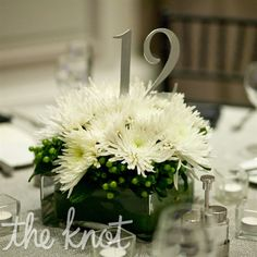 simple, modern arrangements of spider mums accented with small green berries. Leigh found metal table numbers on Etsy.com and spray-painted them silver.