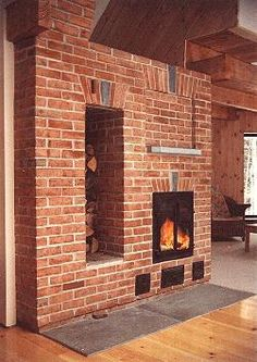 """A custom firebrick core in Jackson, NH with a facade of of Cuswha Rose molded brick. The arch keystones and mantle are soapstone, the hearth is bluestone. The chimney is separated from the heater by 16"""" creating the woodbox. Creating a woodbox in this way is quite cost effective as it results in simply making the connection to the chimney longer. A further benefit is that the side of the firepalce is fully exposed. This allows the stored heat to radiate more effectively into the living…"""