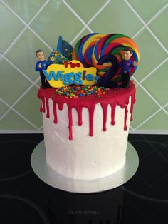 Wiggles 2nd birthday cake-Vanilla Swiss meringue buttercream and truffle ganache drip cake with swirl lollipops confetti chocolate bark and gumpaste logo. Easy but time consuming!