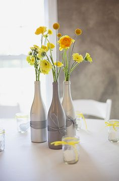 clean, simple, beautiful wine bottle centerpieces. blue bottles w yellow flowers white ribbon?
