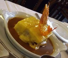 The Francesinha, Portuguese sandwich with bread, ham, sausage, roast meat and covered with molten cheese and a hot thick tomato and beer sauce served with french fries.  The Café Majestic in Porto has the best.
