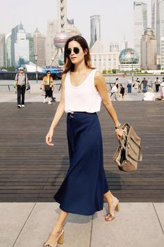 Gala Gonzalez wears a white tank top, navy midi skirt, tan satchel bag, round sunglasses, and neutral heels