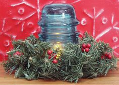 Holiday, vintage glass insulator with flameless candle & greenery.
