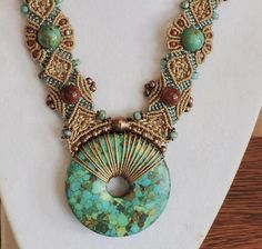 Turquoise Donut Micro-macrame Necklace I knotted this beautiful western-style necklace with a turquoise donut, beige and turquoise c-lon nylon cord, two genuine turquoise large beads, goldstone beads, copper beads, orange rustic seed beads. The colors in this piece would surely