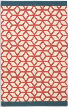 Eisa Teppich. Das geometrische Muster in leuchtendem Korallrot kontrastiert raffiniert mit Akzenten in Petrolblau. Dank abgedunkeltem Weiß eignet sich der Teppich auch für vielbegangene Wohnbereiche.