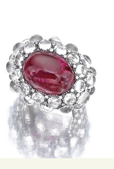 SPINEL, MOONSTONE AND DIAMOND RING, MICHELE DELLA VALLE Set with a cabochon red spinel to a surround of brilliant-cut diamonds and cabochon moonstones, mounted in white gold, size 53, indistinctly signed della Valle and maker's marks, Italian assay and maker's marks, case.