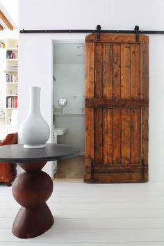 love this reclaimed wood door on the sliding track.  A friend of mine did this at his place and they are beautiful....