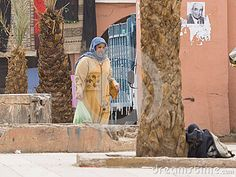 Muslim woman on the side dirty and destroyed street  citie Taroudant in Morocco