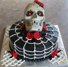 Halloween cake, black with red roses. Skull made of candy, glowing red eyes used lights and painted red.