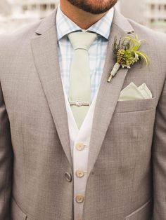 Man in a light gray three piece suit with a blue check shirt and a pale green tie and pocket square