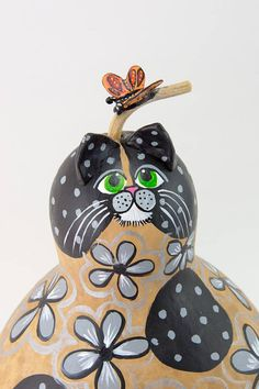Gray Cat comes with fine craftsmanship and a charismatic personality. This cat is made from a dried gourd and embellished with a strong resin clay, acrylics, and several coats of varnish. He promises to light up your room or the cat lover in your life. This cat stands 12 tall and is 7 in