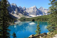 Moraine Lake in Alberta, Canada. Het 14 kilometer lange gletsjermeer wordt nog mooier dankzij de weerspiegeling van de besneeuwde Rocky Mountains.