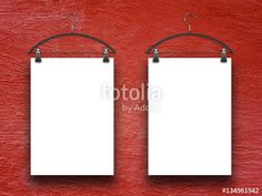 Two blank frames hanged by clothes hangers on red concrete wall background