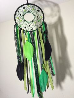 Green and black 5 inch dreamcatcher. Made with various shades of green and black ribbon, beads and feathers.  This dreamcatcher hangs approx.