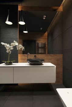 Dark bathroom contrasts white accents and wood