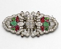 ART DECO DIAMOND AND COLORED STONE DOUBLE-CLIP/BROOCH, CIRCA 1925.  The lozenge-shaped brooch separating into a pair of shield-shaped clips, set with marquise-shaped, baguette and round diamonds weighing a total of approximately 3.50 carats and accented with carved ruby and emerald leaves and round and cushion-shaped demantoid garnets, mounted in platinum.