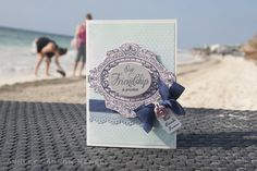 Trim Melissa Frances 5th Avenue patterned paper to about 4″ x 5.75″. Stamp JustRite Vintage Ovals label on Papertrey Ink sweet blush cardstock, then hand cut. Stamp Vintage Ovals sentiment with outdoor denim ink by Close to My Heart onto an oval die cut. Mat on stamped label with foam adhesive. Add navy seam binding around patterned paper. Add American Crafts Dear Lizzy rose bud brad. Stamp sentiment on tag die cut, then attach to ribbon knot. Punch Martha Stewart lace border from…