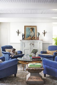 For their living room, the couple reupholstered two 1940s American chairs and a pair of French Art Deco chairs in a hardy textile from Mood Fabrics. Flanked by bronze- and-porcelain French wall sconces from the 1920s, a vintage blue cabinet is a makeshift easel for Woman in a Blouse by Isaac Soyer.