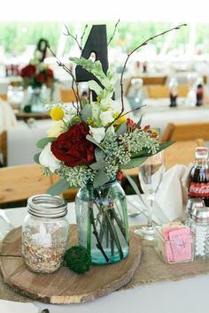 Earthy, summer wedding centerpiece idea - blue tinted mason jar with red flower + greenery on tree slice base {Jennifer Van Elk Photography}