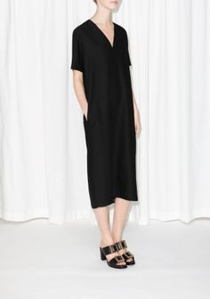 &90 Elegant meets understated in this versatile everyday dress, featuring pockets and split sides that accentuate its relaxed silhouette.