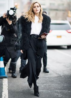 Olivia Palermo gives an almost all-black ensemble head-turning gusto with the right details— fur, a wide belt, an unexpected skirt silhouette, and pointed ankle boots .