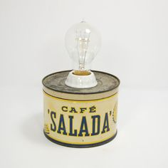 A small table lamp with Edison bulb, upcycled from a vintage coffee can.    Every object tells a story and our coffee can lamps are no exception. Each