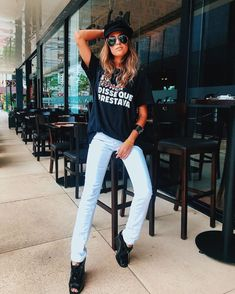 T-SHIRT: MAIS DE UM SÉCULO DE HISTÓRIA! Clássico bem executado! Nada como o combo com o jeans para não errar, né? T-shirt preta com frase de efeito. Serigrafia. Print. Calça jeans. Boina. Óculos escuro. Acessórios. Sapato statement. (Awa Guimarães)
