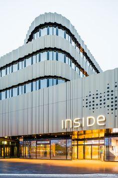 Gallery of INSIDE Boutique Centre / Holzer Kobler Architekturen - 2 gevel schijven materialisatie golfplaat textuur rond inkom sokkel