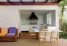 Uma parede com janela e floreira atravancava a área externa, entre a sala de estar e a edícula com a churrasqueira. Sem ela, foi possível criar uma varanda ampla e aconchegante