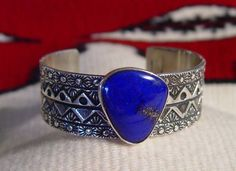 "This bold and handsome bracelet is characteristic of Marc Antia's skill as a silver artisan.  He creates beautifully stamped works of silver.  This exquisite cuff bracelet is showcased by a large central Lapis Lazuli stone with a prominent gold inclusion/vein.    5 3/8"" Bracelet   7/8"" width   1 1/8""  opening   1"" x 1"" Stone  Marc will occasionally add gold to the silver to create a unique piece of art especially when he uses turquoise or coral in the design.  When you invest in a piece of…"