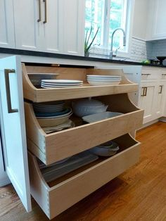 Kitchen Pull-out Drawers. Underneath you can open up the two doors to reveal three large pull out drawers that house my large serving dishes. No more being on your hands and knees trying to pull them out from the bottom of the cabinets, I literally can open the drawers up and see what I need. The sides of the pullouts are staggered so you can see in easily too. The countertop cabinet doors fold back onto themselves to tuck out of the way Kate Abt Design. #KitchenPullOutDrawers…