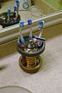 Toothbrush holder made from a few gears, a spring and a lug nut. Clear coated with automotive grade clear.