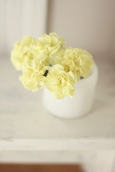 Butter yellow carnations in a vintage cold cream pot