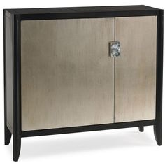 For this small but perfectly proportioned closed storage unit, an asymmetrical pair of doors features dramatic custom Mother of Pearl hardware. Two latch panels at the top open with slight pressure revealing a sleek cubby with a multi-plug electrical outlet designed for recharging electronic devices. A felt tray slides from side to side and has individual sections for loose change or keys. The unit includes multiple storage drawers and trays behind each door, as well as necklace or tie hooks…