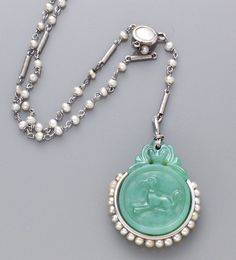 An art deco jadeite jade, seed pearl and platinum necklace the seed pearl and platinum link chain suspending a jadeite jade disk, carved with a bird and a dog, framed by seed pearl