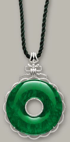 JADEITE AND DIAMOND 'BI' PENDANT The circular Bi of translucent emerald green colour with streaks of rich green colour, decorated by pear-shaped, circular- and rose-cut diamonds together weighing approximately 2.60 carats, strung on a green cord, mounted in 18 karat white gold, length approximately 620mm.