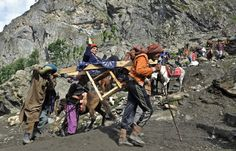 Hindu pilgrims are transported by Muslim porters from Pishu Top, some 127 kms southeast of Srinagar, India, during the annual Hindu pilgrimage to the holy cave shrine of Amarnath.