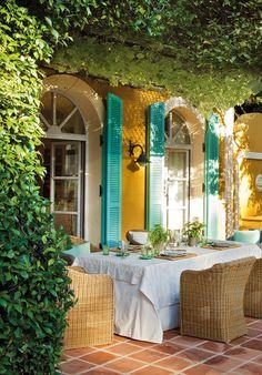 Ventanales con palilleria y puertas mallorquinas en turquesa. Sombra vegetal. Muebles de rafia