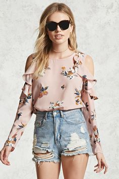 A woven top featuring an allover floral print, an open shoulder with a ruffle trim, long sleeves, a round neckline, back button closure with a keyhole cutout, and a curved hem.