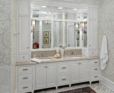 great use of space with linen storage, wrap around mirrors, and sconces.  Love the wallpaper too!