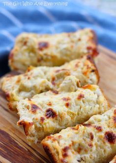 KILLER ARTICHOKE BREAD:Ingred:1/4 cup butter;   3 garlic cloves, minced;1 (14-ounce) can marinated artichoke hearts, drained well and chopped;1 cup (4 ounces) shredded Mozzarella cheese;1/2 cup (2 ounces) shredded Cheddar cheese; 1 cup grated Parmesan cheese;1/2 cup sour cream;1 French bread loaf (about 12 ounces);Salt and freshly ground black pepper; OINK! OINK! OINK! OINK!