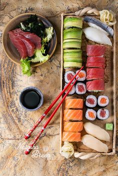 Sushi set nigiri, sashimi and rolls on clay plate served with chopsticks and soy sauce on stone surface. Flat lay.