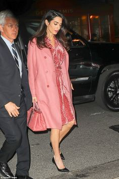 Elegant: Amal matched her rosy pink lipstick to her eye-catching ensemble, wearing her glossy locks in bouncy curls