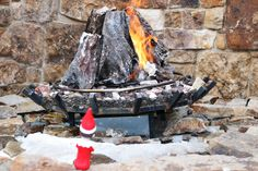 Alfonz sitting by the fire in Mountaineer Square Courtyard #elfontheshelf #crestedbutte