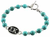 Swarovski Turquoise Beads, and Swarovski Crystals are combined to create our Sigma Kappa Bracelet. The Sorority bracelet top is cast in solid sterling silver and hand finished to achieve maximum detail. The Turquoise beads are Swarovski dyed Howlite with a bright Turquoise color and a hint of natural looking matrix. The accent beads are genuine Swarovski Crystal in a clean Aqua color.