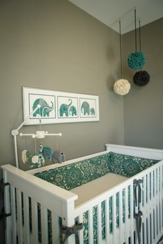 This gray nursery is super soothing with lots of turquoise,white furniture, and elephants.