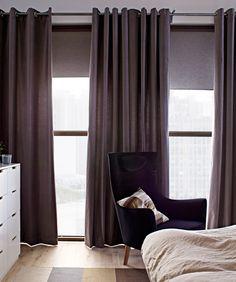 Ein Fenster mit SANELA Gardinenpaar in Grau.