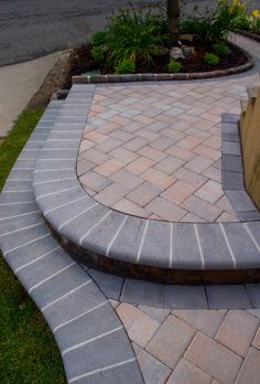 Gassib Construction created this artistic hardscape from the entrance to the rear for this Ridgefield, NJ home on the Palisades. Paving Stones: The Sherwood Collection with ArmorTec/Ledgestone; XL; 3-Pc.; Design Kit; Color: Toffee/Onyx Lite; Border: The RoundTable Collection with ArmorTec; 6x9; Color: Onyx; Wall Stones: Cambridge MaytRx Wallsystem, Stretcher Double-Sided Wall Stone; Color: Toffee/Onyx; Caps & Steps: The Crusader Collection with ArmorTec-Bullnose Shape; 6x12; Color: Onyx;