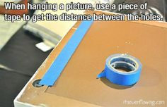 Use a piece a tape to measure distance between two holes when hanging a picture.